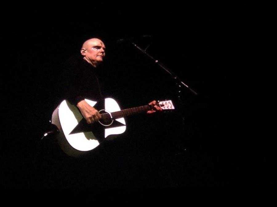 Billy Corgan playing an acoustic guitar