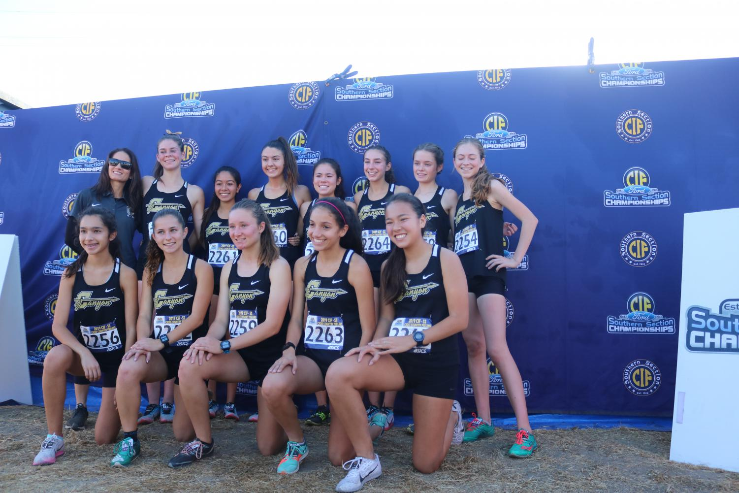 Girls varsity cross country pose for a photo after getting second place.