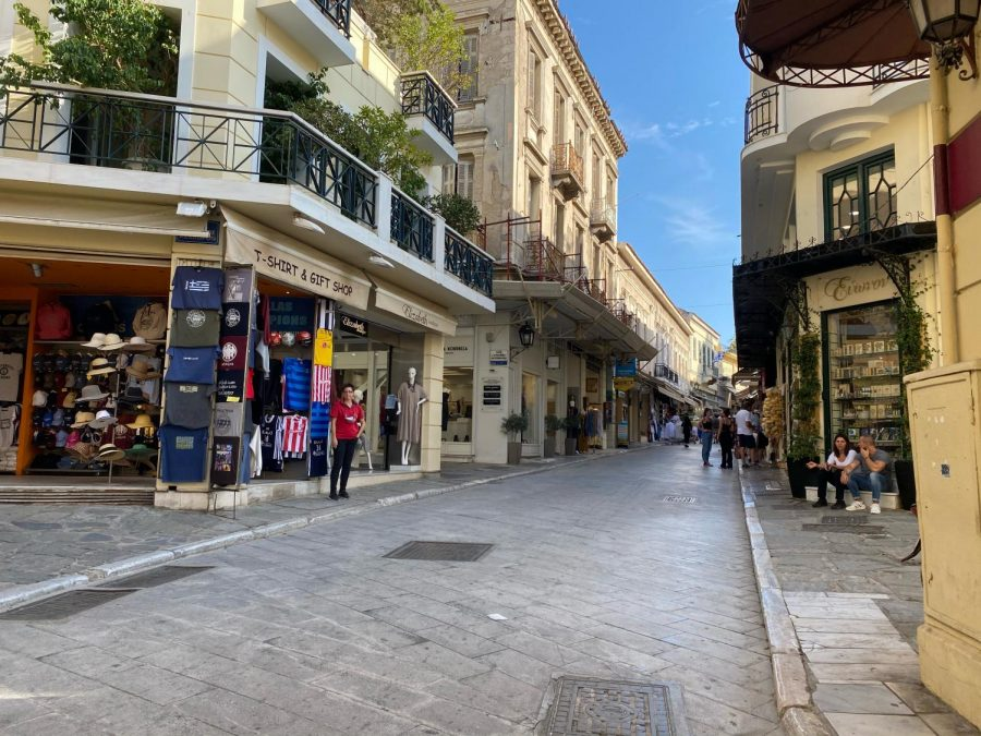 A few people walk down a mostly empty shopping street in Athens.